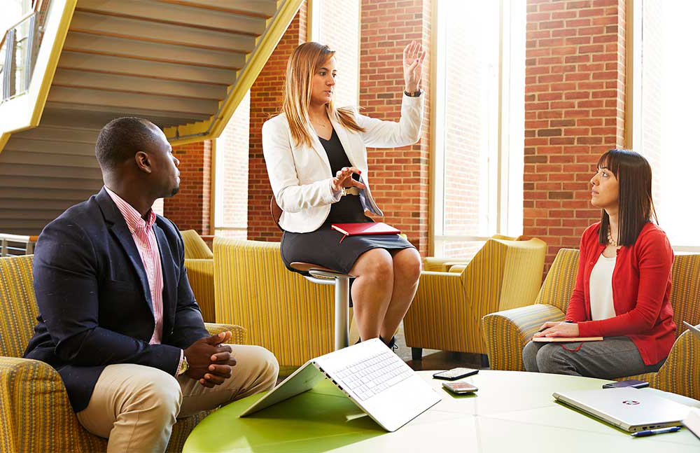 three well-dressed students around a conference table discussing