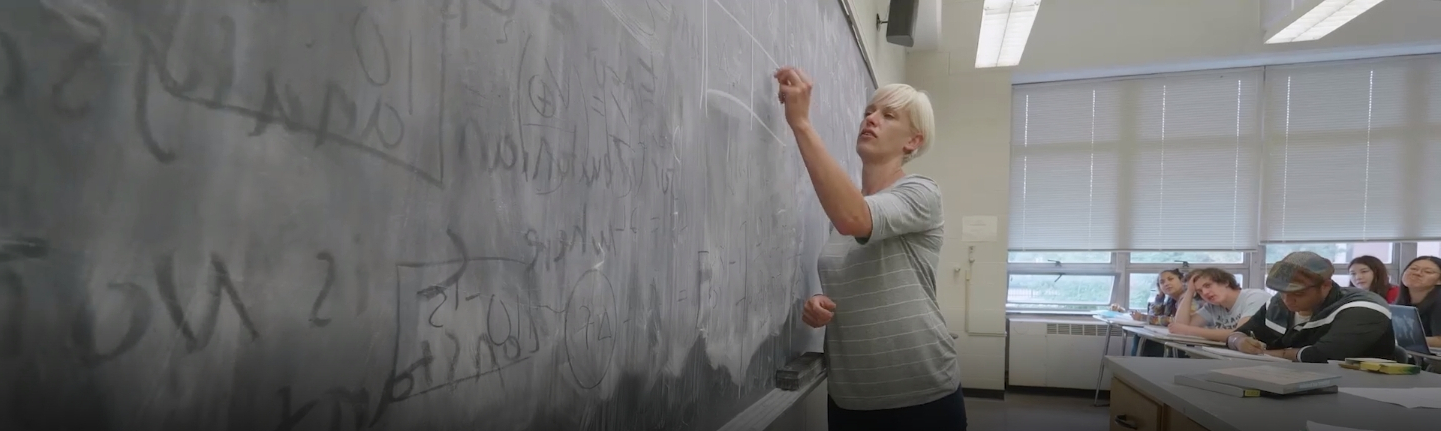 professor writing on a blackboard