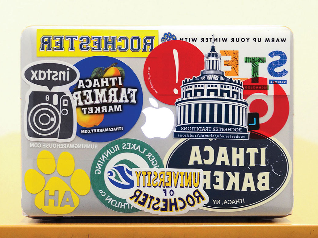 laptop covered in stickers with Rochester themes.