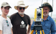 three people pose for a photo with a surveyor tool.